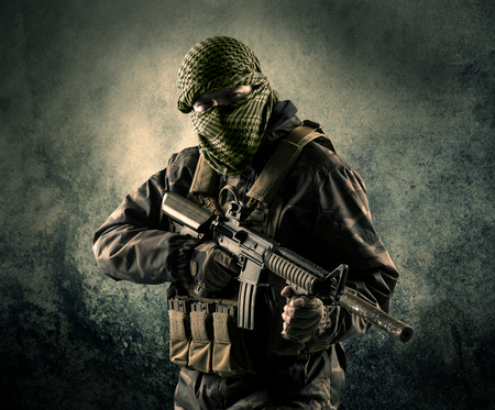 Portrait of a heavily armed masked soldier with grungy background