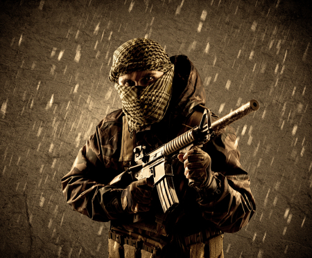 Dangerous heavily armed terrorist soldier with mask on grungy rainy background Banque d'images
