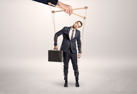 Puppet businessman leaded by a huge hand Stockfoto