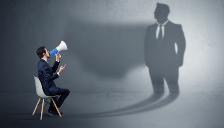 Businessman staying and offering stuffs to a huge businessman shadow