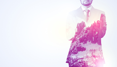 Young businessman in suit standing with sunny snowy mountain and trees graphic. Archivio Fotografico
