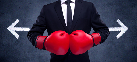 A confident businessman standing with red boxing gloves on his hand in front of arrows pointing in different directions on urban wall background concept. Фото со стока