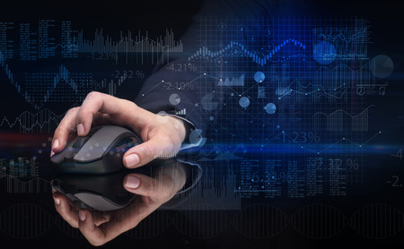 Hand using wireless mouse with financial concept on dark background  Stock Photo