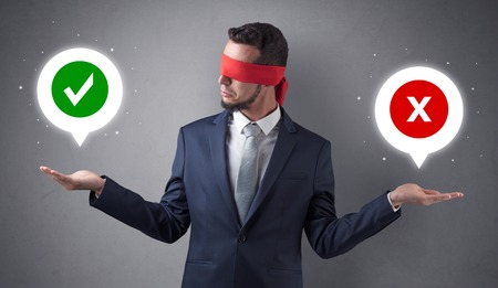 Blindfolded businessman trying to choose Standard-Bild