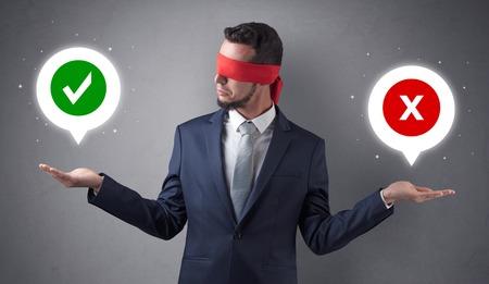 Blindfolded businessman trying to choose Foto de archivo