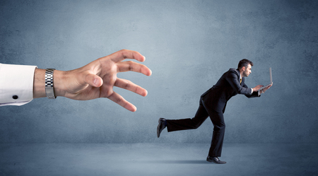 Businessman running from hand