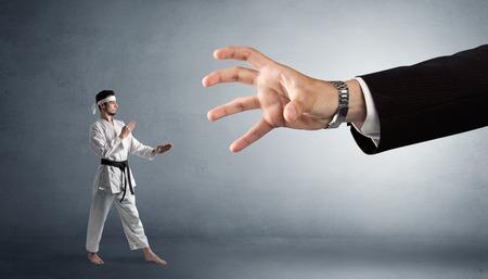 Big hand catching small karate man
