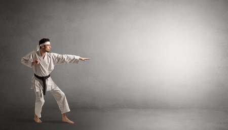 Small karate man fighting in an empty space