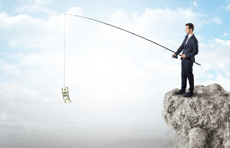 Businessman fishing dollar from a rock