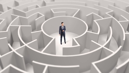 Businessman standing in a middle of a round maze 写真素材