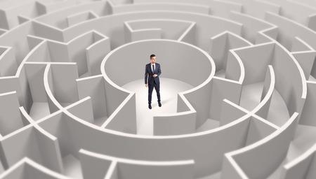 Businessman standing in a middle of a round maze Standard-Bild