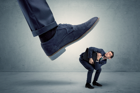 Employee getting trampled by big shoe Stock Photo - 103089833
