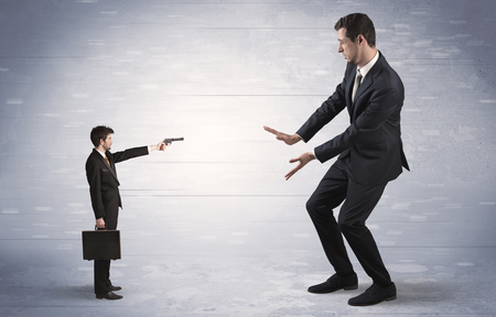 Small businessman shooting giant businessman Stock Photo