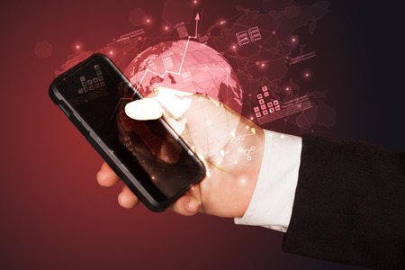 Hand using phone  with worldwide reports links and statistics concept Foto de archivo