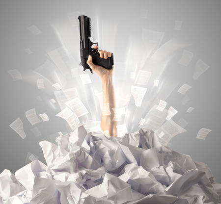 Hand coming out from paper pile