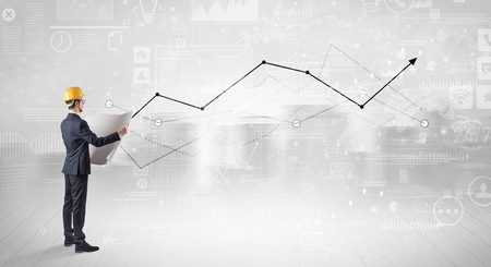 Engineer holding a plan and standing with graphs, charts and reports on the background Stock Photo