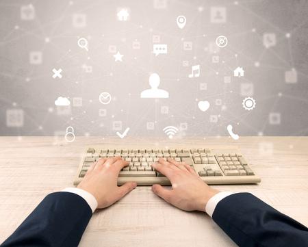Elegant businessman hand typing social media icons around Stock Photo