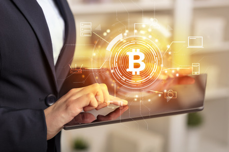 Business woman using tablet in home office mood with bitcoin link network concept Stock Photo
