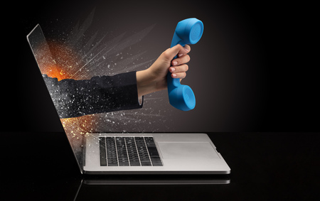 Hand with phone coming out of a laptop Stock Photo