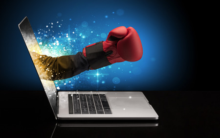 Hand with box gloves coming out of a laptop Stock Photo