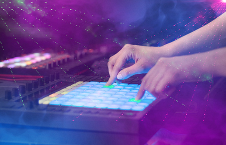 Hand mixing music on djcontroller with party club colors around