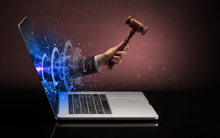 Hand with hammer coming out of a laptop Stock Photo