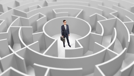 Businessman standing in a middle of a round maze Stock Photo