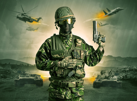 Armed soldier standing in the middle of a war Stock Photo