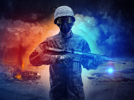 Armed soldier standing in the middle of dust storm Stock Photo