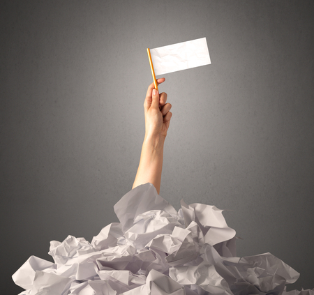 Female hand emerging from crumpled paper pile holding a white blank flag Stock Photo