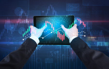 Hand holding tablet with global reports and stock market change concept