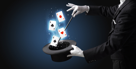 Magician making trick with wand and playing cards Banque d'images