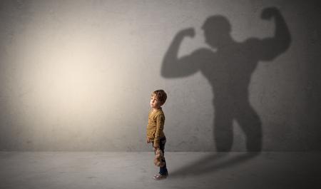 Muscleman shadow behind waggish little boy Stock Photo