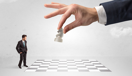 Little businessman playing chess with a big hand concept Stok Fotoğraf