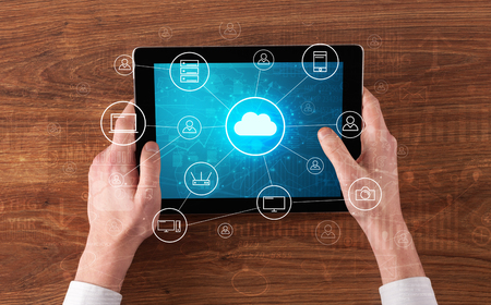 Hand touching tablet with cloud computing and online storage concept 版權商用圖片