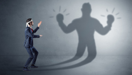 Businessman fighting with his unarmed shadow Stock Photo