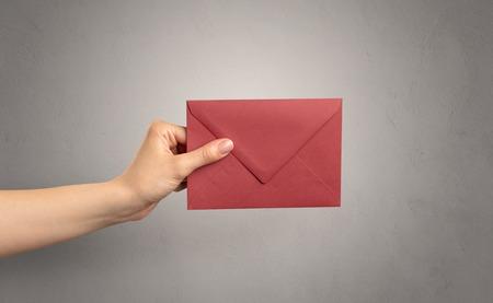 Hand holding envelope with empty wall background Reklamní fotografie - 106744594