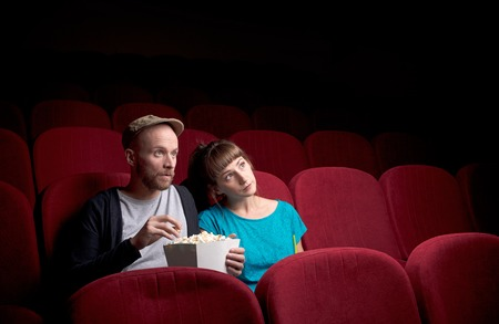 Young couple sitting at red movie theatre Stock Photo