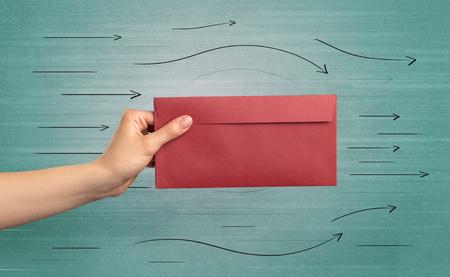 Hand hält Umschlag mit Pfeilen herum