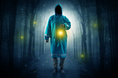 Mysterious man coming from a path in the forest with glowing lantern concept