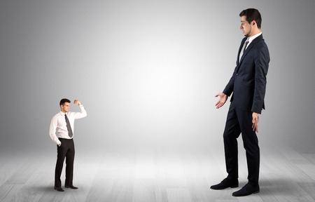 Giant businessman scared of small businessman Archivio Fotografico