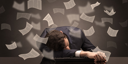 Businessman fell asleep at the office with paperwork concept