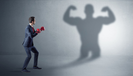 Businessman fighting with his bossy shadow Фото со стока