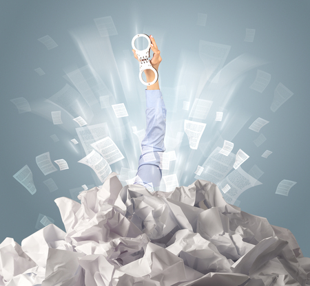 Hand coming out from paper pile Stock Photo - 117369244