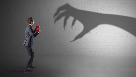 Businessman fighting with scary hand shadow