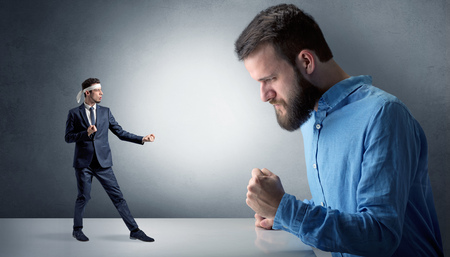 Giant man yelling at a small karate man Stock Photo