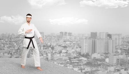 Karate man doing karate tricks  on the top of a metropolitan city