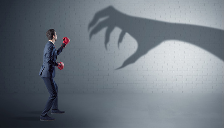 Businessman fighting with scary hand shadow Фото со стока - 108294992