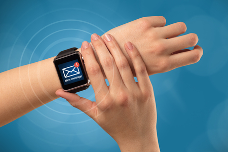 Hand with smartwatch and blue background 写真素材