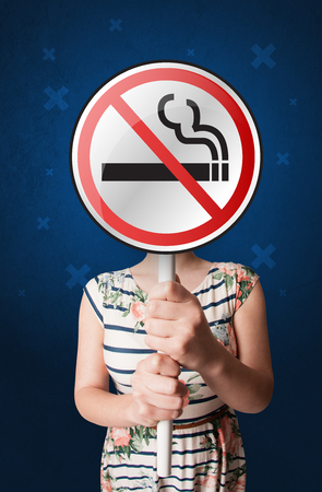 Casual young woman holding round sign with no smoking graphic 写真素材